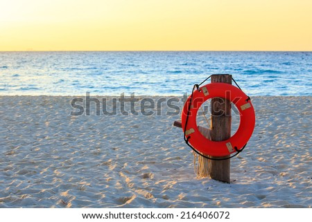 Life preserver on sandy beach somewhere in Mexico - stock photo