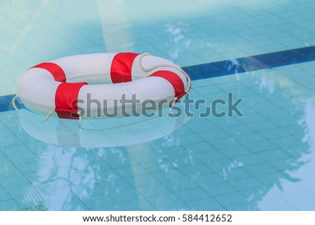 Life Ring on blue water at the swimming pool .ring buoy a life saving buoy designed to be thrown to a person in the water