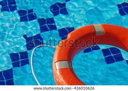 Life ring swims on a surface of blue water in the pool. Life Ring on blue water. - stock photo