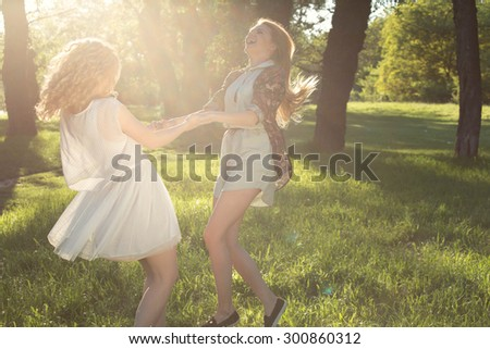 Life's about the little things. Two beautiful blond girls holding each others hands, smiling and having fun in the park. Best friends enjoying a beautiful summer day. - stock photo