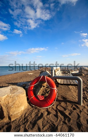 Life Saver on the Beach under a Blue Sky - stock photo