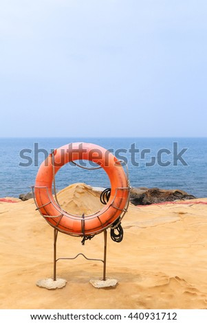 Life Saving Ring or Life Preserver Hanging on Steel Stand on Sandy Coast at Yehliu Geopark, Taiwan. Tourists Visit to See a number of Rock Formation along the Cape. - stock photo