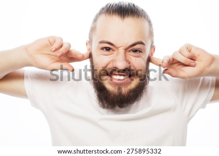 life style and people concept: frustrated bearded man in white shirt holding fingers in his ears and keeping eyes closed while standing against white background - stock photo