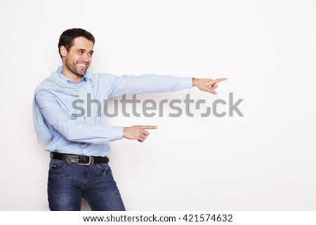 life style, business  and people concept: Young smiling man points with fingers in the right side on white background. - stock photo
