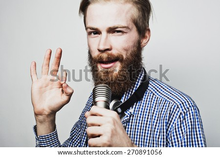 Life style concept: a young man with a beard wearing a white shirt holding a microphone and singing. Over gray background. Special Fashionable toning photos. - stock photo