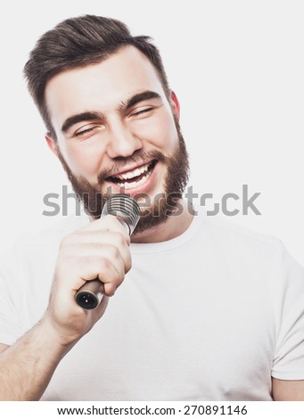 Life style concept: a young man with a beard wearing a white shirt holding a microphone and singing.Isolated on white. Special Fashionable toning photos. - stock photo