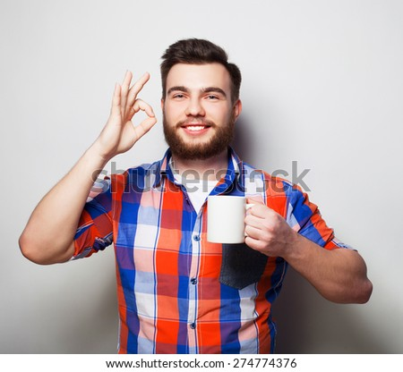 life style, happiness and people concept: young bearded man with a cup of coffee in hand and showing okey, against grey background. - stock photo