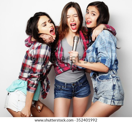 life style, happiness, emotional and people concept: beauty hipster girls with a microphone singing and having fun - stock photo