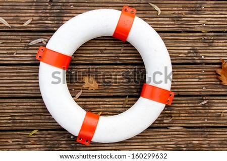 Lifebelt on wooden background - stock photo