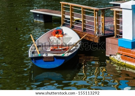Lifeboat On Duty. Closeup view of a safety boat docked to a quay in the public pond on a sunny simmer day. Nobody in sight. Reflections of light in water. - stock photo