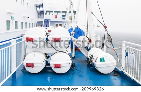 Lifeboats (barrel) by deck of a cruise ship - stock photo