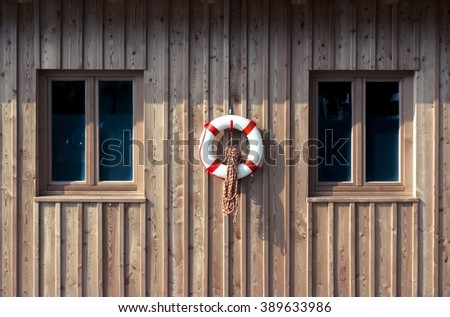 Lifebuoy between two windows on a wooden wall - stock photo