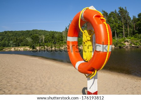 Lifebuoy in orange, suspended on a pole, the position of the rescuer on the river. - stock photo