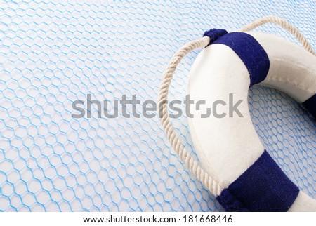 Lifebuoy on a blue grid over white background. - stock photo