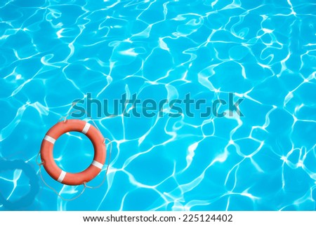 Lifebuoy on blue water surface - stock photo