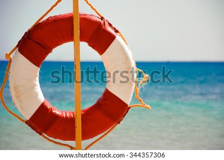 Lifebuoy On Sandy Beach on a stick - stock photo