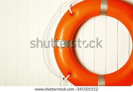 Lifebuoy on wooden wall - stock photo
