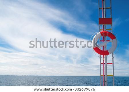 Lifebuoy, Red and White Life Preserver by the Seashore of Coastal Summer Vacation Resort - stock photo