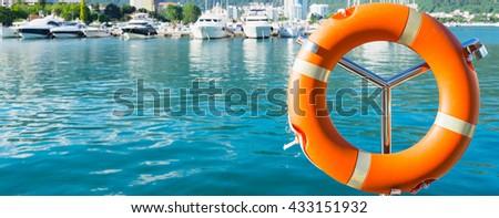 Lifebuoy with  blured yacht on the background. Photo taken in Budva, Montenegro. - stock photo