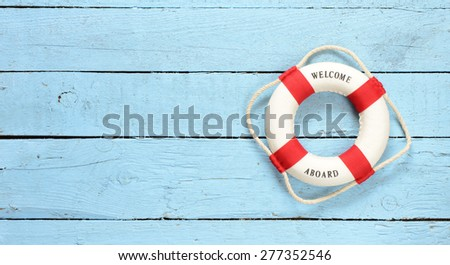 Lifebuoy with Welcome on Board phrase on wooden background - stock photo