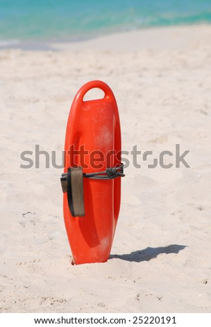 Lifeguard buoyancy aid sticking in the sand - stock photo