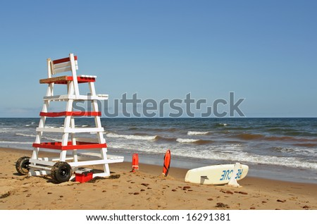 lifeguard chair and beach rescue tools on ocean shore - stock photo