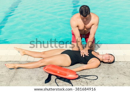 Lifeguard doing resuscitation procedure. Toned image - stock photo