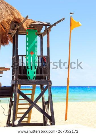 Lifeguard hut and yellow flag on caribbean beach - stock photo