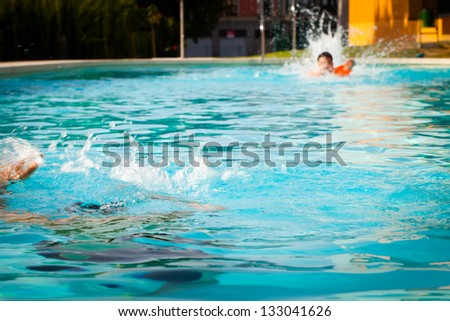 Lifeguard swimming to save a drowned man in a swimming pool. - stock photo