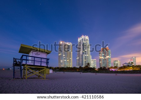 Lifeguard tower in a typical colorful Art Deco style at sunshine, with blue sky and modern residential buildings in the background. World famous travel location. Miami beach, Florida.  - stock photo