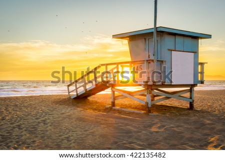 Lifeguard Tower on the Beach at Sunset with the Sun shining through. - stock photo