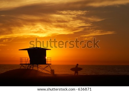 Lifeguard tower with setting sun on the horizon and the silhouette of the surfer - stock photo