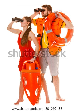 Lifeguards with rescue tube ring buoy lifebuoy and life vest jacket looking through binoculars. Man and woman supervising swimming pool. Accident prevention. - stock photo