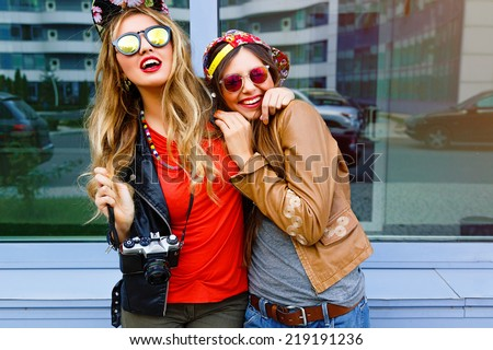 Lifestyle bright urban portrait of two bear fiends. Two pretty girls wearing swag hipster neon hats and sunglasses, hugs and having great time together, city window background. - stock photo