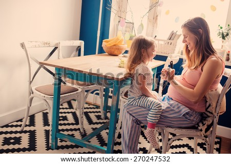 lifestyle capture of pregnant mother and baby daughter having fun in kitchen in the morning - stock photo