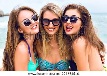 Lifestyle close up fashion portrait of three pretty girls best friends having fun smiling and posing on camera at the beach near ocean, wearing stylish bright bikini and sunglasses. - stock photo