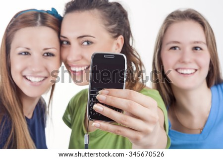 Lifestyle Concept and Ideas. Three Beautiful Caucasian Ladies Taking Selfie Photos With Smartphone. Isolated Over White. Horizontal Image Orientation - stock photo