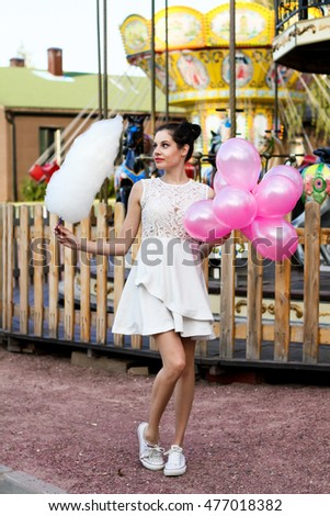 Lifestyle concept, attractive teenager with colorful latex balloons in the amusement park near carousel with cotton candy