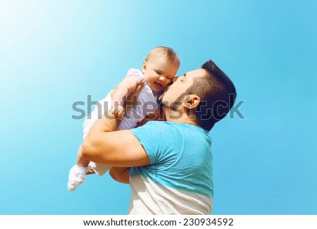 Lifestyle family photo happy father kissing baby outdoors against on summer sunny blue sky - stock photo