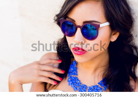 Lifestyle fashion portrait of stylish  young asian woman in trendy sunglasses ,bright  necklace  posing  outdoor . Summer bright colors.