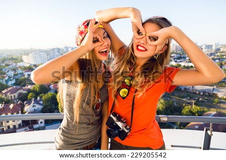 Lifestyle fashion portrait of two cheerful pretty best friends girls making funny faces and going crazy together, wearing bright clothes, holding retro camera and posing on the roof. - stock photo