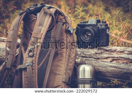 Lifestyle hiking camping equipment retro photo camera backpack and thermos outdoor forest nature on background - stock photo