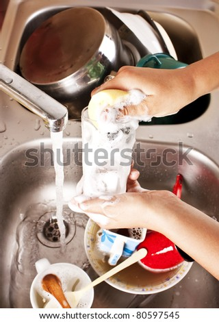 LIFESTYLE IMAGE-a woman washing a dish - stock photo