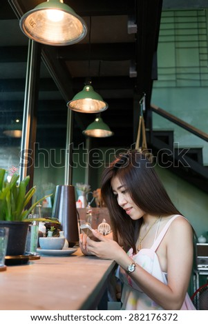 lifestyle of women using a mobile phone in cafe coffee shop with texting message on app smartphone playing social network - stock photo