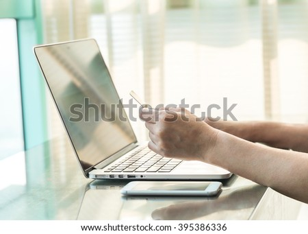 Lifestyle person hand holding credit card using computer for wifi internet IT IOT SEO online market shopping advertising: Buyer/ customer typing security number order goods/ booking from home office  - stock photo