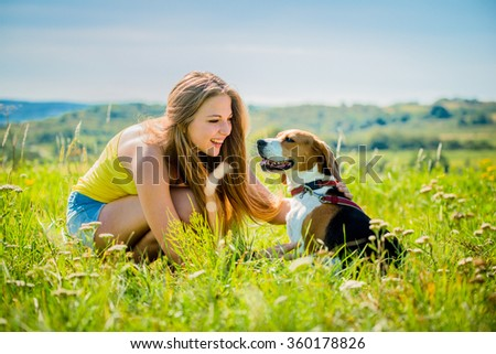 Lifestyle photo of happy young girl with her pet (beagle dog) - outdoor in nature