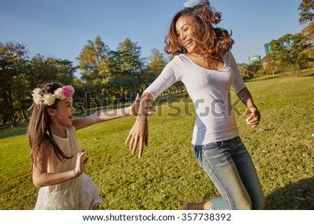 Lifestyle portrait mom and daughter in happines at the outside in the meadow - stock photo
