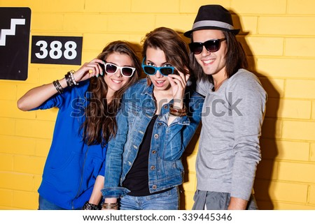 Lifestyle portrait of beautiful adult hipsters wearing stylish bright outfits and sunglasses and having great time. Poses for the camera in front of yellow brick wall enjoying day off and have fun. - stock photo