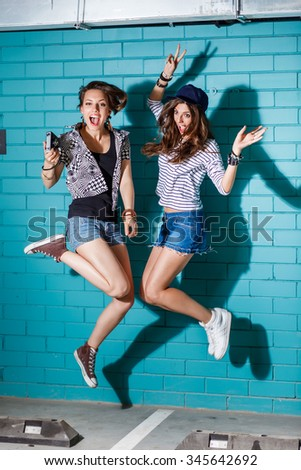 Lifestyle portrait of beautiful best friends hipster girls wearing stylish bright outfits and having great time. Jumping together in front of blue brick wall and have fun. Young active happy people. - stock photo