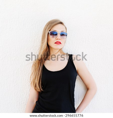 Lifestyle portrait of beautiful blonde girl posing outside. Red lips, long hair, wearing sunglasses. - stock photo